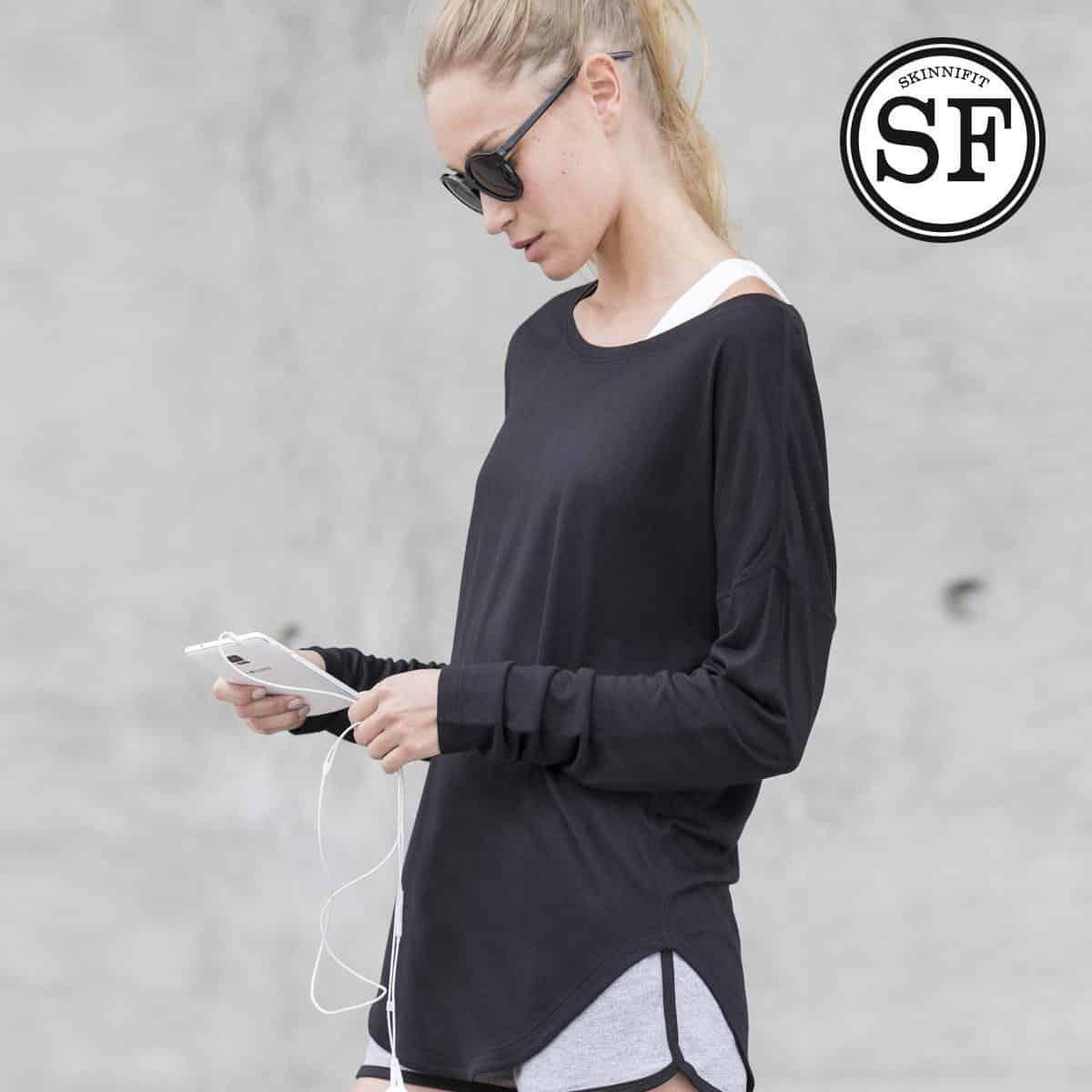 Ragazza bionda con coda di cavallo e occhiali scuri con smartphone e auricolari