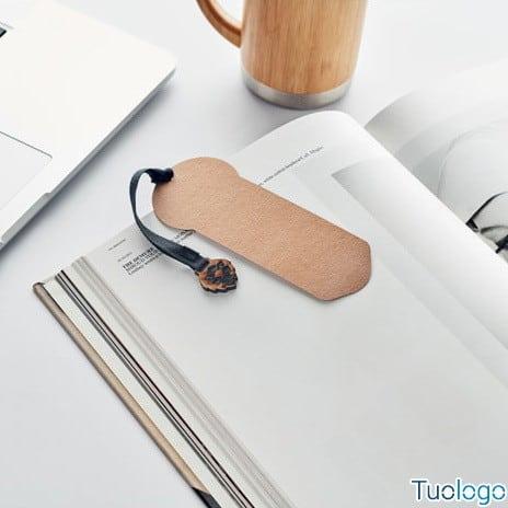 Segnalibro in carta con cordino in cotone e semi di pino su un libro