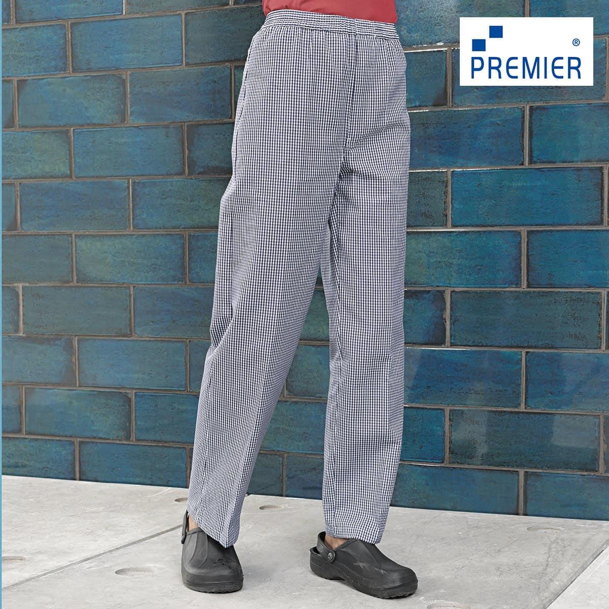 Dettaglio gambe uomo con pantaloni cuoco quadretti bianchi blu con sandali parete di piastrelle blu