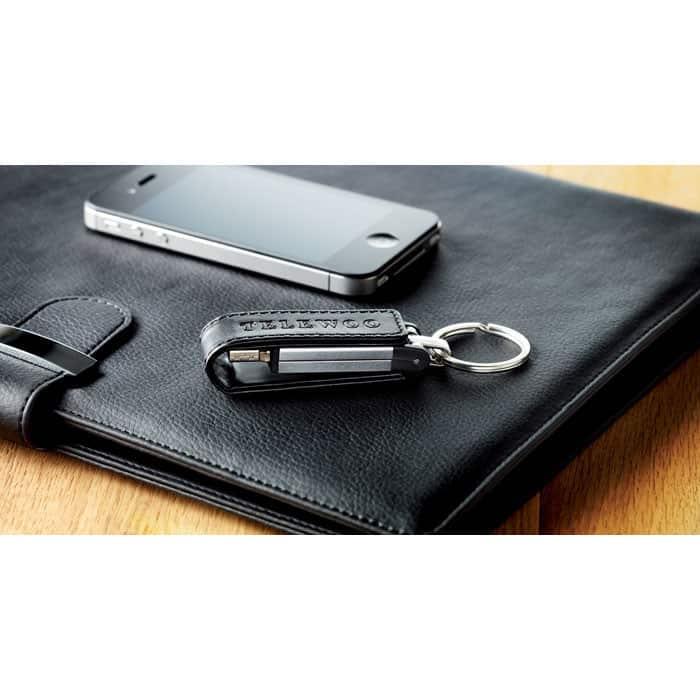 Chiavetta usb in metallo e pelle nera con anello portachiavi sopra un'agenda