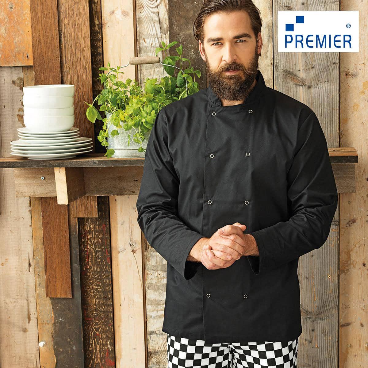 Cuoco con barba e capelli raccolti, con pantaloni a scacchi, giacca nera con collo alla coreana e manica lunga