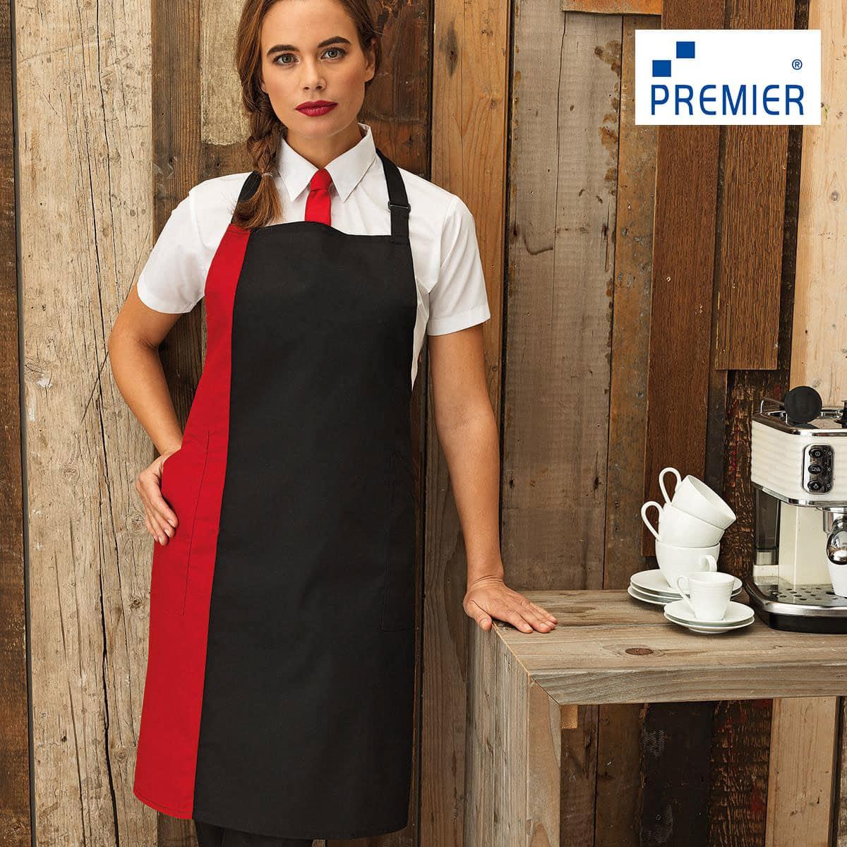 Ragazza con treccia e grembiule rosso e nero, appoggiata a un bancone con tazze e macchina espresso