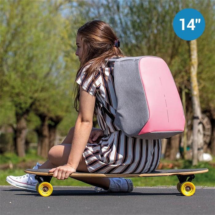 Ragazza seduta su uno skateboard con zaino rosa antitaccheggio
