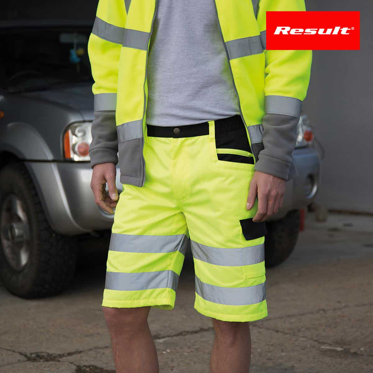 Dettaglio vita di un uomo con pantaloncini e gilet da lavoro giallo fluo con bande riflettenti