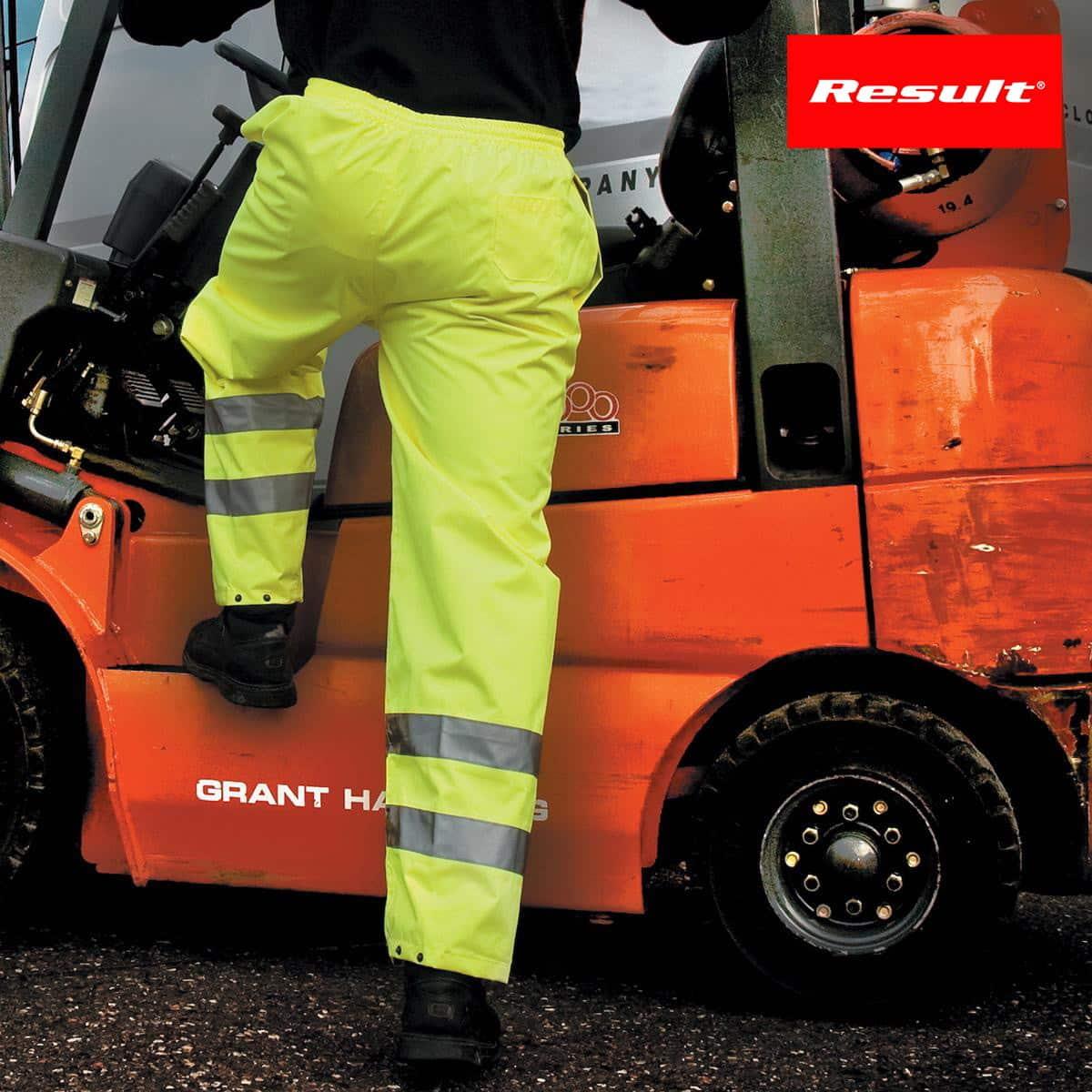 Dettaglio gambe di uomo con pantalone giallo fluo e bande riflettenti che sale su muletto