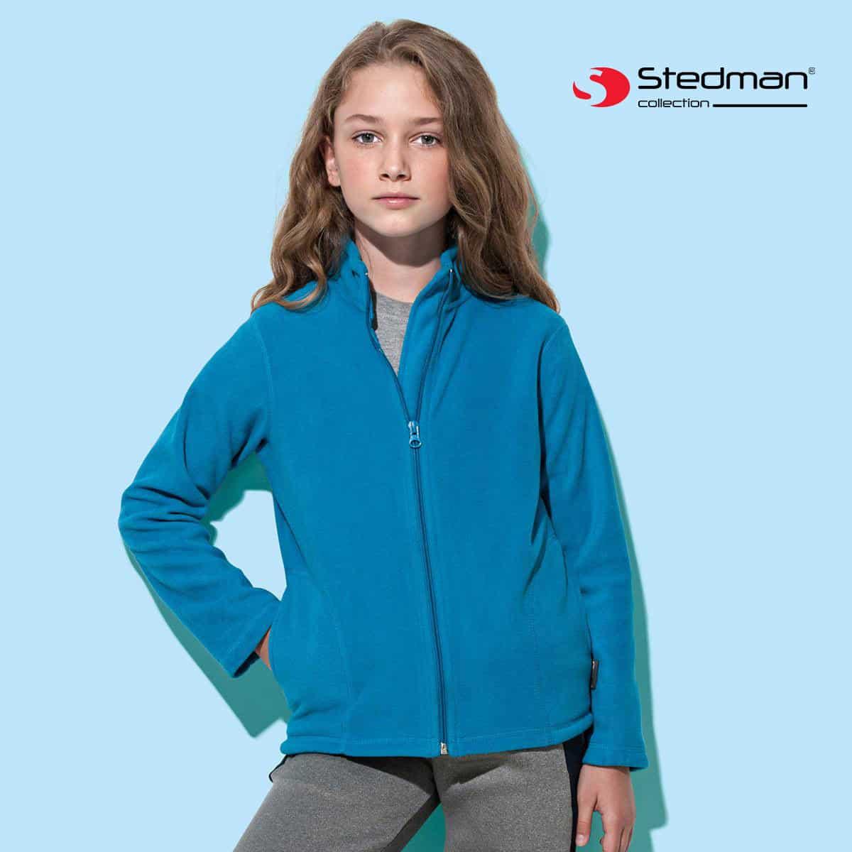 Bambina con lunghi capelli biondi pantaloni grigi e pile collo alto con zip lunga turchese