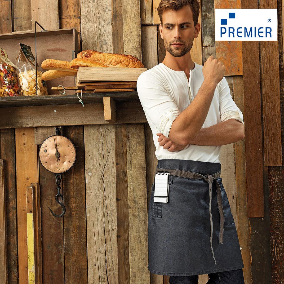 Ragazzo con maglia panna, grembiule in jeans e blocco alla cintura sfondo di legno con mensole